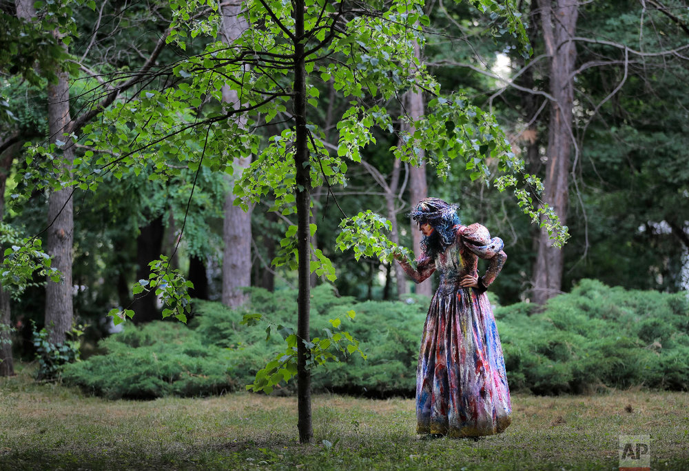 Marta Teresa da Rocha, of Spain's Alucinarte Animacion Teatral walks in a park before performing in the Living Statues International Festival, in Bucharest, Romania on Sunday, May 27, 2018. (AP Photo/Vadim Ghirda)