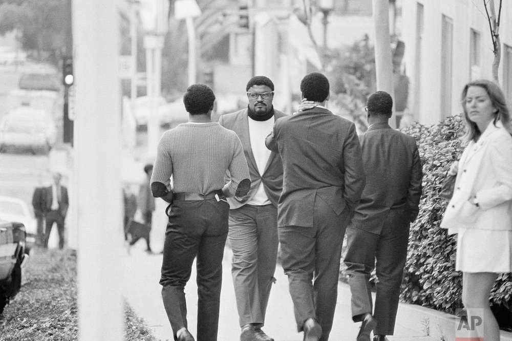 Football player Roosevelt Grier, credited with assisting in the capture of the man held as a suspect in the shooting early today June 5, 1968 of Sen. Robert Kennedy, takes a few steps backwards as he and companions leave the hospital in Los Angeles where Kennedy has undergone surgery. Rafer Johnson, the Olympic decathlon champ, and Grier both were credited for helping capture and hold the suspect. (AP Photo)