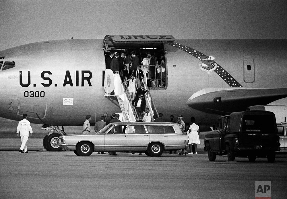 Children of Sen. and Mrs. Robert F. Kennedy arrive, June 5, 1968 at Andrews Air Force Base, Maryland near Washington, after an evening flight from Los Angeles where their father was shot earlier in the day. Coming down the ramp of an Air Force plane are, from bottom, Kerry, 8 assisted by an unidentified aide; Michael, 10, Courtnay, 11, and David, 13. Others inside plane include astronaut John Glenn, back to camera, assisting Christopher, 4. (AP Photo/Charles Harrity)
