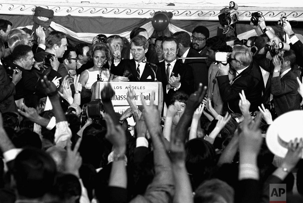 This June 5, 1968 photo shows Sen. Robert F. Kennedy speaking his final words to supporters at the Ambassador Hotel in Los Angeles, moments before he was shot on June 5, 1968. At his side are his wife, Ethel, left, and his California campaign manager, Jesse Unruh, right. Football player Roosevelt Grier is at right rear. Associated Press Hollywood reporter Bob Thomas was on a one-night political assignment in June 1968 to cover Kennedy's victory in the California presidential primary when mayhem unfolded before his eyes. (AP Photo/Dick Strobel)