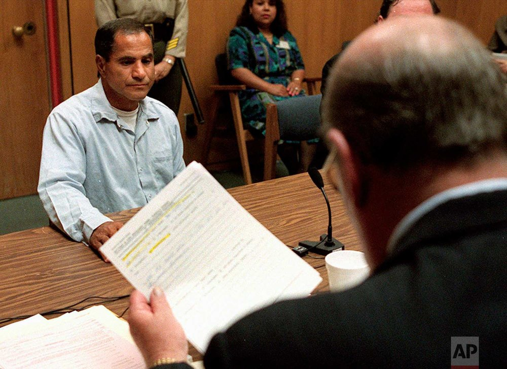 In this June 18, 1997 photo, Sirhan Sirhan, left, listens as Steve Baker, right, one of three counselors at his parole hearing, reads the decision to not parole the man convicted of killing Robert F. Kennedy, in Corcoran, Calif. Mayor Sam Yorty and Police Chief Tom Reddin told a news conference in June 1997 that Sirhan, 23, was traced through the .22 pistol used to wound Kennedy and five others, less seriously, and identification was made through a brother, Adel Sirhan, of Pasadena. (AP Photo/Eric Paul Zamora)