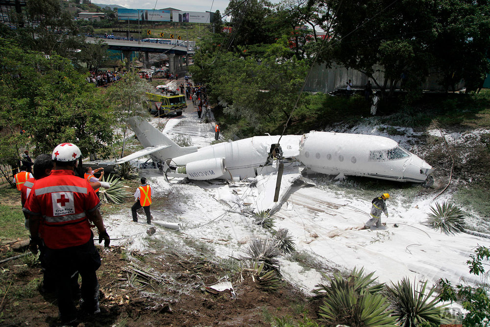 A white Gulfstream jet lies broken in half and engulfed in foam sprayed by firefighters, in Tegucigalpa, Honduras, Tuesday, May 22, 2018. The private jet crashed off the end of the runway, but the crew and passengers were rescued and out of danger, according to Honduras emergency management agency. (AP Photo/Fernando Antonio)