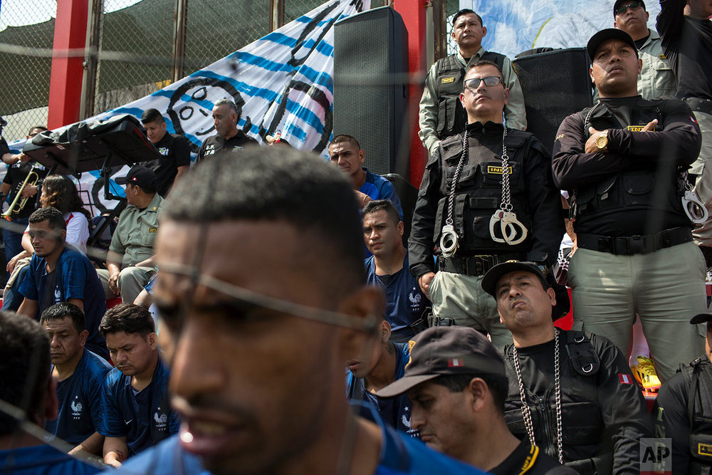 Inmates escorted by prison guards watch a soccer match in the San Juan de Lurigancho prison, in Lima, Peru, Thursday, May 24, 2018. Inmates of 17 prisons, including four for women, participated in the First Interprison World Cup Lima 2018, organized by the National Penitentiary Institute. (AP Photo/Rodrigo Abd)