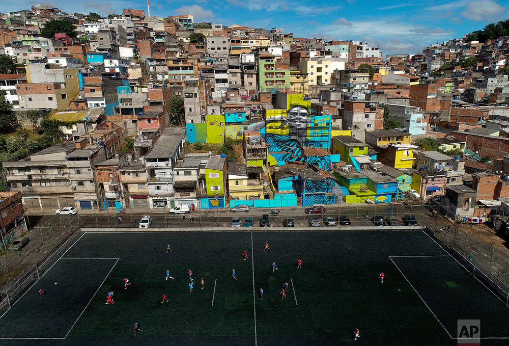 Neighborhood kids play soccer in the Jardim Peri neighborhood where professional soccer player Gabriel Jesus grew up and is featured in a mural on the side of homes in Sao Paulo, Brazil, Sunday, May 20, 2018. (AP Photo/Andre Penner)