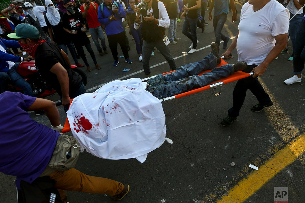 A demonstrator who was fatally shot in the head is carried by paramedics after clashes during a march against Nicaragua's President Daniel Ortega in Managua, Nicaragua, Wednesday, May 30, 2018. Violence returned to protests against Ortega's government when riot police and government supporters confronted anti-government protesters during a mothers day march to commemorate those mothers who has lost children during the ongoing protests. (AP Photo/Esteban Felix)