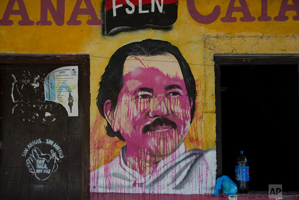 A mural of Nicaraguan President Daniel Ortega is defaced at a campaign house for the Sandinista National Liberation Front (FSLN) in Catarina, Nicaragua, Monday, May 7, 2018, the morning after anti-government demonstrators clashed with FSLN supporters and police. Deadly protests amid a harsh government crackdown weakened Ortega, one of the few leftist leaders remaining in power in Latin America, forcing him to pull back on social security reforms that sparked the unrest and facing a newly emboldened opposition determined to see him leave office. (AP Photo/Moises Castillo)