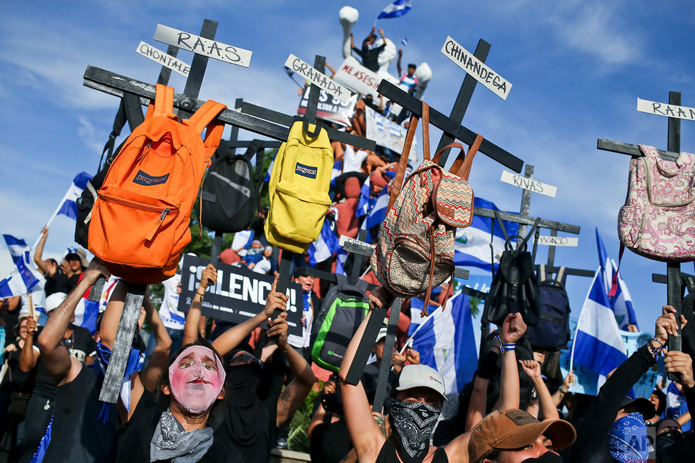 University students hold up backpacks soon crosses, representing killed student protesters, as they march against Nicaragua's President Daniel Ortega in Managua, Nicaragua, Wednesday, May 30, 2018. The march ended in violence, as influential business leaders called for early elections to resolve a political standoff between Ortega's government and protesters demanding his exit from office. (AP Photo/Esteban Felix)