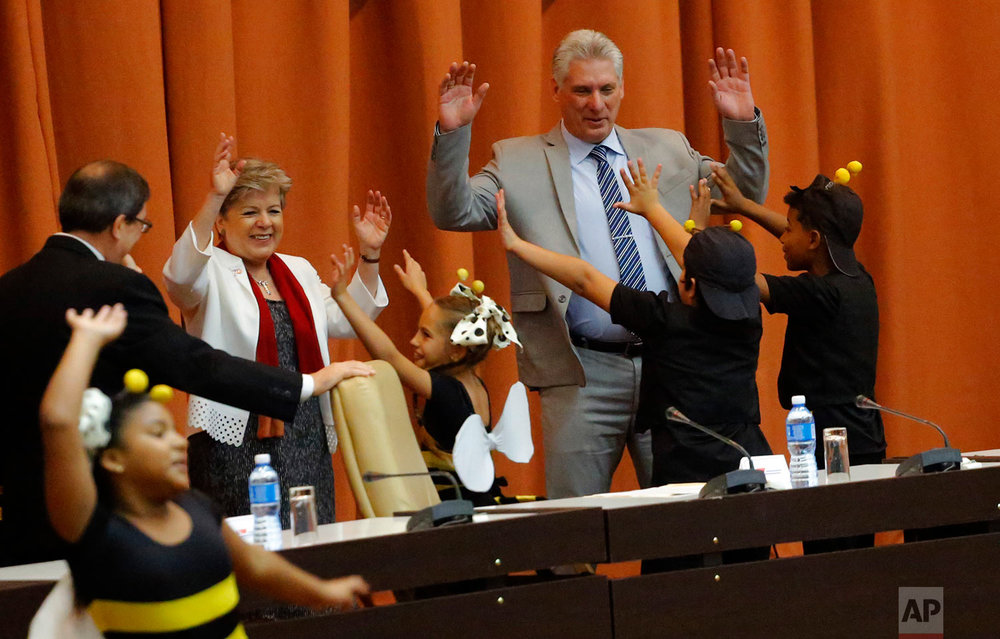 "Cuba's President Miguel Diaz-Canel, right, dances with children from the theater group ""La Colmenita"" at the opening session of the economic commission's biennial meeting in Havana, Cuba, Tuesday, May 8, 2018. The Castros' successor as president has broken from the immediate past, and made clear to Cubans that he will be operating far more like a conventional modern politician than the spotlight-shy general who selected him. (AP Photo/Desmond Boylan)"