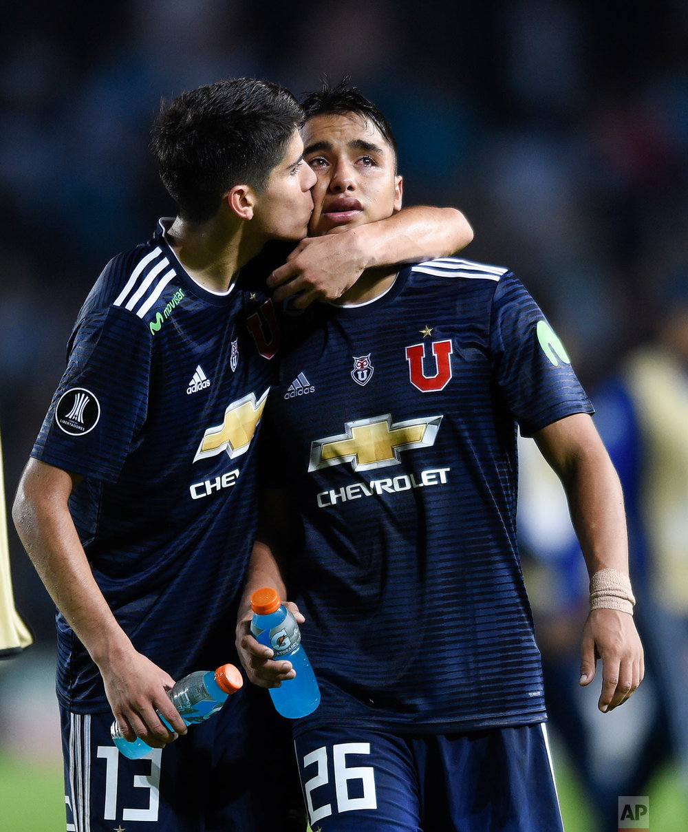 Nicolas Guerra Ruz gets a kiss from teammate Angelo Araos, of Universidad de Chile, after they lost 0-1 to Racing Club a Copa Libertadores soccer match in Buenos Aires, Argentina, Thursday, May 3, 2018.(AP Photo/Gustavo Garello)