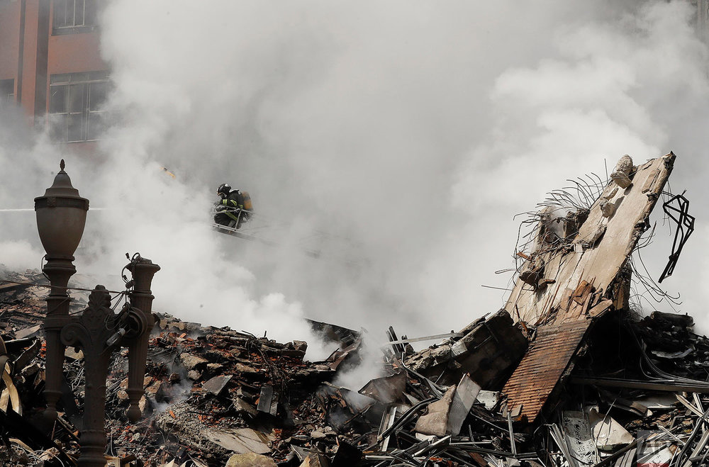 Firefighters work in the the rubble of a building that caught fire and collapsed in Sao Paulo, Brazil, Tuesday, May 1, 2018. The building collapsed as firefighters worked to put out the flames. (AP Photo/Andre Penner)