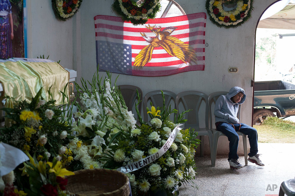 A boy attends the wake of slain Guatemalan immigrant Claudia Gomez Gonzalez at her parents' home where they use an American flag as a curtain, in San Juan Ostuncalco, Guatemala, Friday, June 1, 2018. The 19-year-old, who was fatally shot by a U.S. Border Patrol agent in Texas on May 23, had graduated as a forensic accountant but was unable to attend college or find a job, so she had left Guatemala for the U.S., according to her aunt. (AP Photo/Moises Castillo)