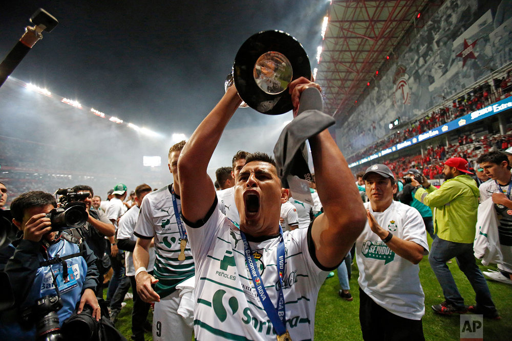 Santos' Osvaldo Martinez holds his team's championship trophy after winning the Mexican soccer final against Toluca in Toluca, Mexico, Sunday, May 20, 2018. (AP Photo/Rebecca Blackwell)