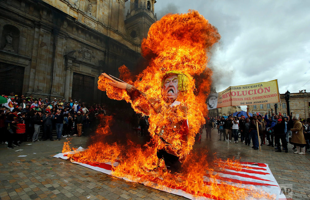 Protesters burn an effigy of U.S. President Donald Trump during a demonstration marking May Day to honor workers in Bogota, Colombia, Tuesday, May, 1, 2018. (AP Photo/Fernando Vergara)