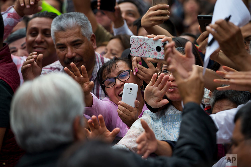 People greet presidential candidate Andres Manuel Lopez Obrador who arrives for his campaign rally in Mexico City, Monday, May 7, 2018. Mexico will choose a new president in general elections on July 1. (AP Photo/Rebecca Blackwell)