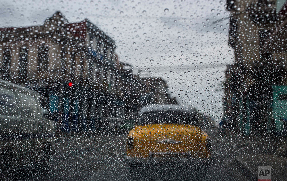 Rain drops accumulate on a car's windshield as commuters wait at a red light in Havana, Cuba, Thursday, May 24, 2018. (AP Photo/Desmond Boylan)