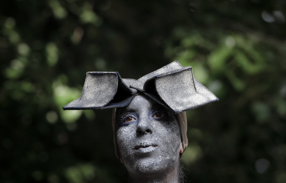 In this Sunday, May 27, 2018, photograph, an artist of Romania's Masca theatre wears an outfit inspired by famous Romanian sculptor Constantin Brancusi's iconic Endless Column, at the Living Statues International Festival, in Bucharest, Romania.(AP Photo/Vadim Ghirda)