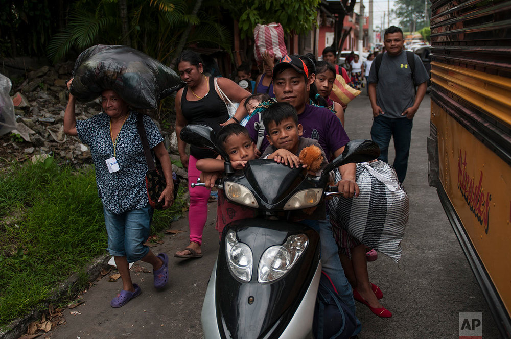 Residents evacuate after a new flow of searing hot volcanic material moved down the slopes of the Volcano of Fire in Escuintla, Guatemala, Tuesday, June 5, 2018. (AP Photo/Oliver de Ros)