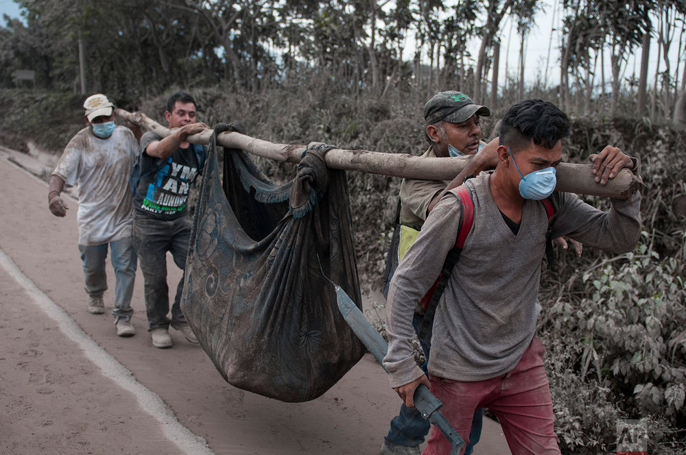 "Residents carry a body recovered near the Volcan de Fuego, or ""Volcano of Fire,"" in Escuintla, Guatemala, Monday, June 4, 2018. (AP Photo/Oliver de Ros)"