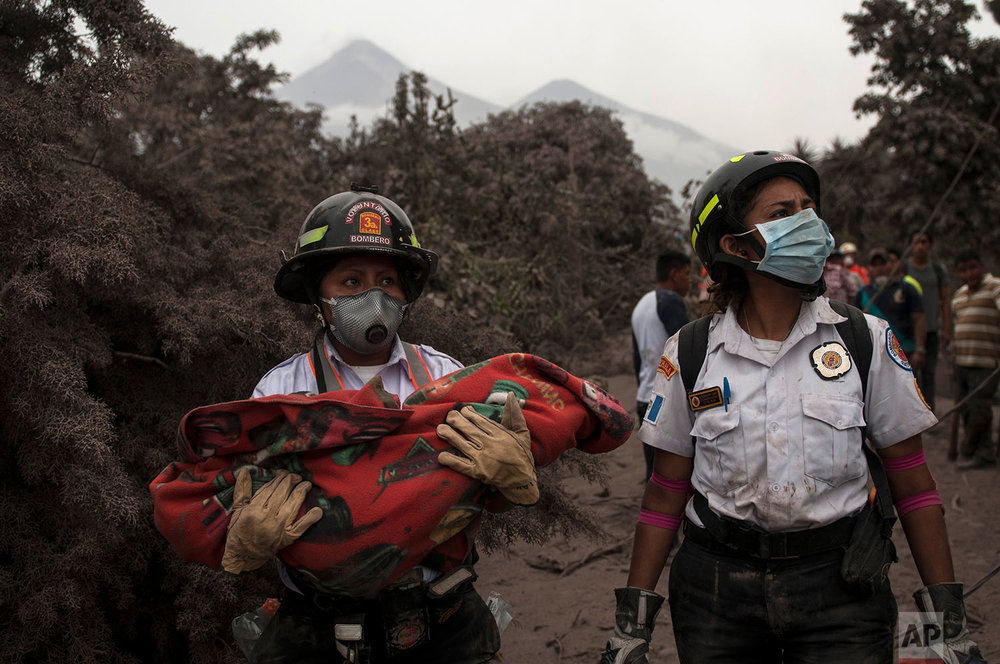 A firefighter carries the body of a child recovered near the Volcan de Fuego, which means in Spanish Volcano of Fire, in Escuintla, Guatemala, Monday, June 4, 2018.  (AP Photo/Oliver de Ros)