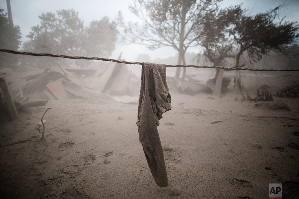 "A pair of pants hang near a destroyed home in the disaster zone covered in volcanic ash near the Volcan de Fuego, or ""Volcano of Fire,"" in the El Rodeo hamlet of Escuintla, Guatemala, Tuesday, June 5, 2018.  (AP Photo/Rodrigo Abd)"