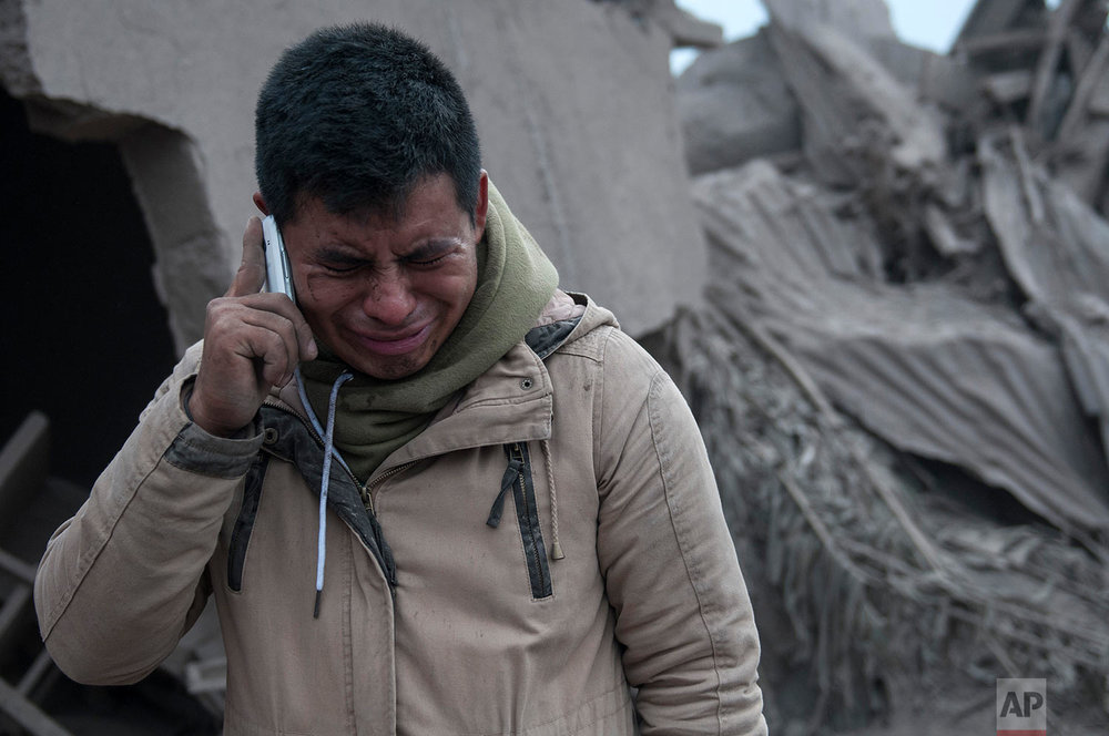 "Boris Rodriguez, 24, who is searching for his wife, cries after seeing the condition of his neighborhood, destroyed by the erupting Volcan de Fuego, or ""Volcano of Fire,"" in Escuintla, Guatemala, Monday, June 4, 2018. (AP Photo/Oliver de Ros)"