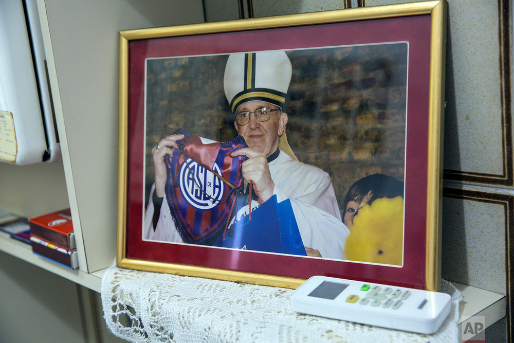 A framed photograph of Pope Francis shows him holding a San Lorenzo soccer logo, on display at the home of soccer fan Josesito Haydossian in Buenos Aires, Argentina, April 14, 2018. (AP Photo/Rodrigo Abd)