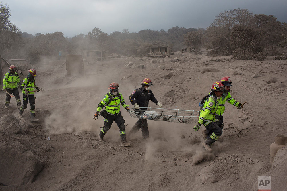 "Rescue workers run for cover as the Volcan de Fuego, or ""Volcano of Fire,"" blows more clouds of ash in the El Rodeo hamlet of Escuintla, Guatemala, Tuesday, June 5, 2018. The fiery volcanic eruption on Sunday in south-central Guatemala killed scores as rescuers struggled to reach people where homes and roads were charred and blanketed with ash. (AP Photo/Rodrigo Abd)"