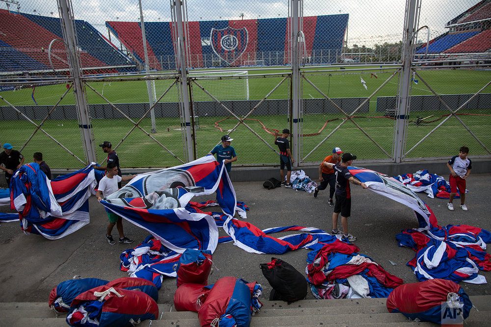 "In this April 11, 2018 photo, San Lorenzo soccer fans from the team's most militant fan base, who call themselves ""La Butteler,"" unfurl flags in the grandstand hours before the start of a match against Brazil's Atletico Mineiro, in Buenos Aires, Argentina. (AP Photo/Rodrigo Abd)"