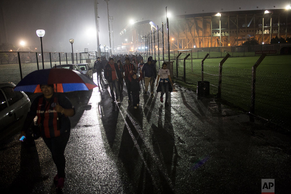 In this May 4, 2018 photo, San Lorenzo soccer fans leave the stadium after their team's 2-0 victory over Belgrano de Cordoba, a game played despite the rain, in Buenos Aires, Argentina. (AP Photo/Rodrigo Abd)