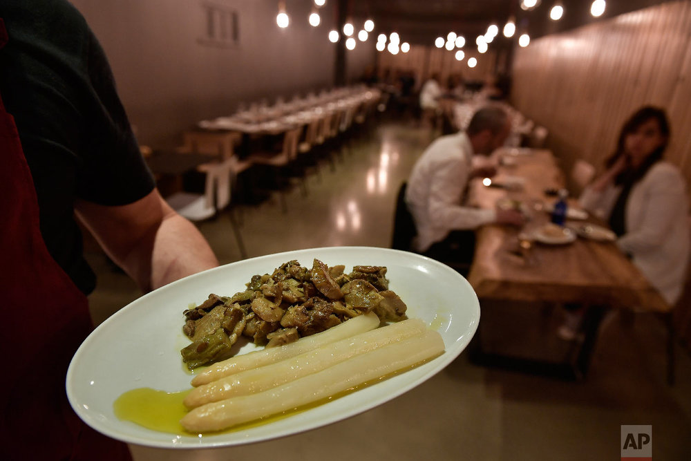 A cook holds a plate with white asparagus ready to be eaten, at a restaurant in Pamplona, northern Spain on Friday, June 1, 2018. (AP Photo/Alvaro Barrientos)