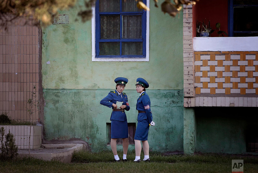 Traffic policewomen chat next to a residential building while off duty in Pyongyang, North Korea, on Oct. 18, 2016. (AP Photo/Wong Maye-E)