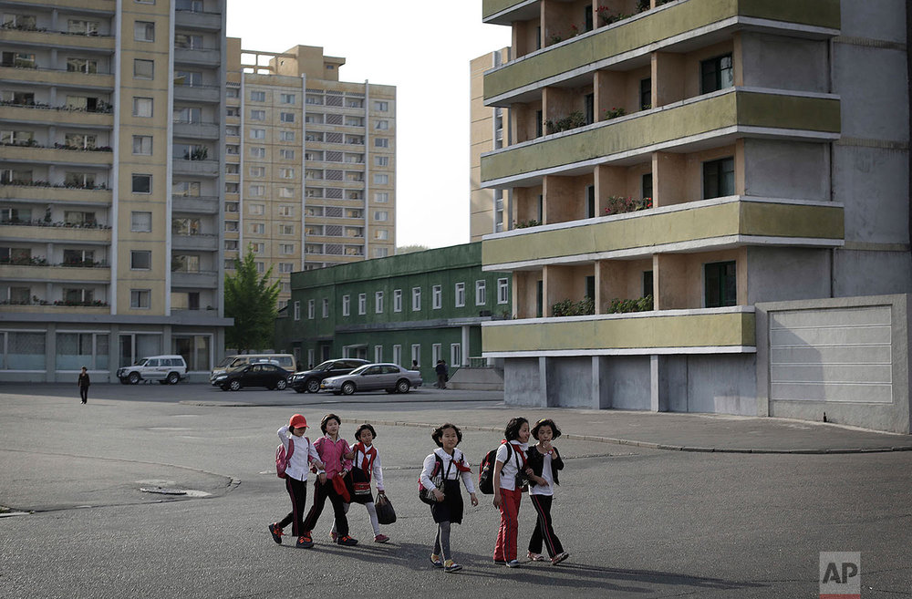 School children walk past an apartment complex in Pyongyang, North Korea, on May 5, 2015. (AP Photo/Wong Maye-E)