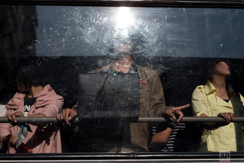 Commuters stand on a bus in Pyongyang, North Korea, on June 24, 2013. (AP Photo/Alexander F. Yuan)