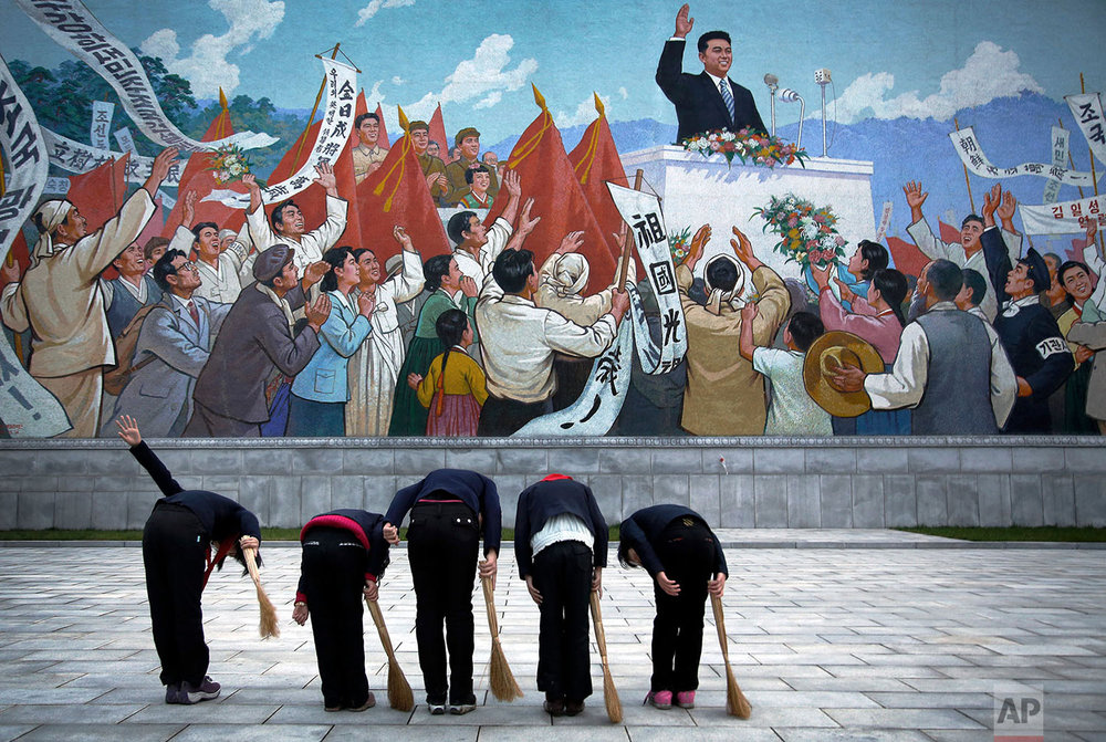 School girls holding brooms bow to pay their respects toward a mural that depicts the late North Korean leader Kim Il Sung delivering a speech, before sweeping the area surrounding the mural on Dec. 1, 2015, in Pyongyang, North Korea. (AP Photo/Wong Maye-E)
