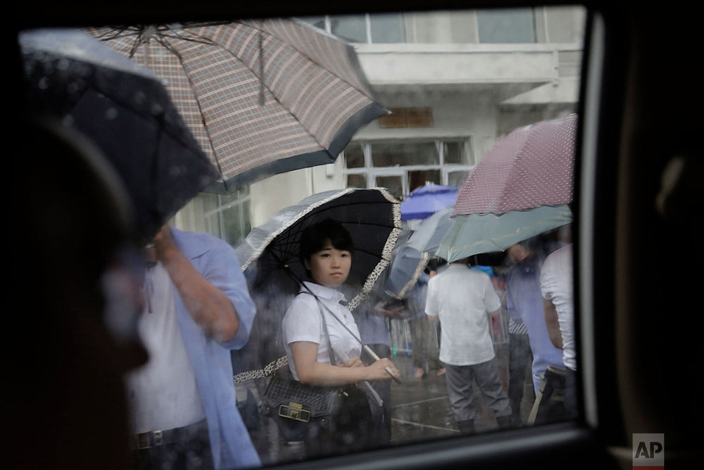 A woman waits in the rain outside a restaurant in Pyongyang, North Korea, on July 25, 2015. The rainy season in North Korea usually lasts through the month of July. (AP Photo/Wong Maye-E)