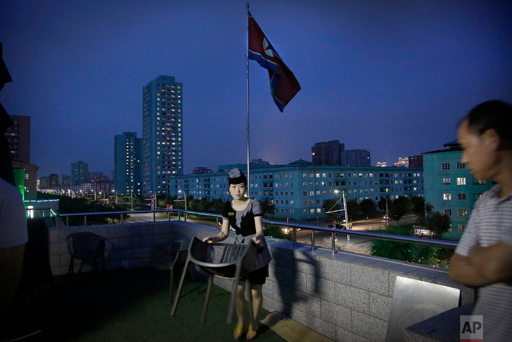 A waitress moves a dining chair at a restaurant terrace that overlooks a residential street at dusk in Pyongyang, North Korea, on June 19, 2017. (AP Photo/Wong Maye-E)