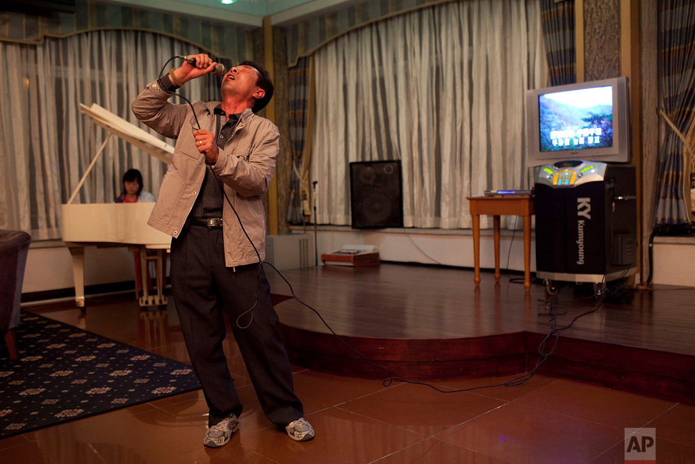 A man sings karaoke while his daughter plays piano at a hotel bar in Mount Kumgang, North Korea, on Oct. 7, 2011. (AP Photo/David Guttenfelder)