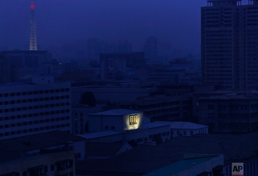 Portraits of the late North Korean leaders Kim Il Sung, left, and Kim Jong Il glow on the facade of a building at dawn in Pyongyang, North Korea, on Aug. 19, 2015. The Juche Tower, one of the city's landmarks, glows in the background at top left. (AP Photo/Dita Alangkara)
