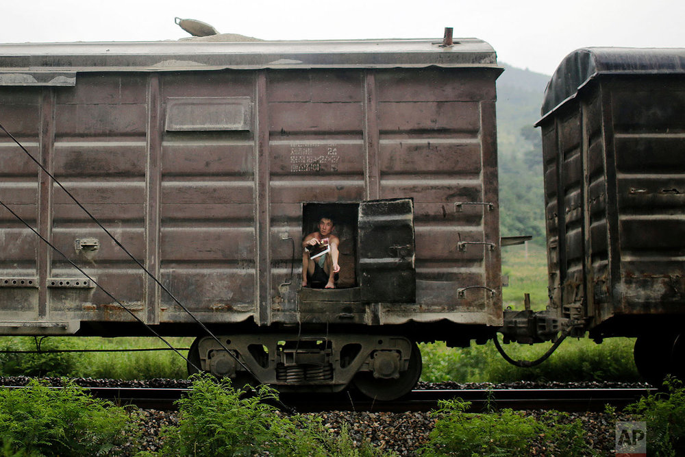 A man sits in the car of a cargo train traveling toward Pyongyang along the outskirts of Hamhung, North Korea, on July 21, 2017. (AP Photo/Wong Maye-E)