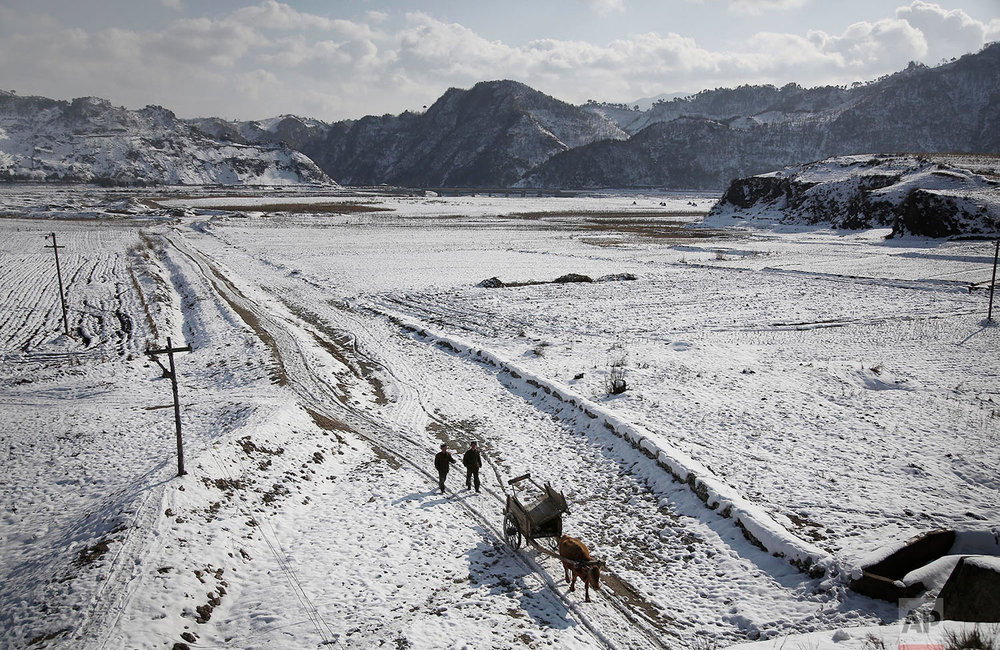 Two farmers walk between snow-covered fields on Dec. 3, 2015, in Kujang county in North Pyongan, North Korea, where the winter season has begun. (AP Photo/Wong Maye-E)