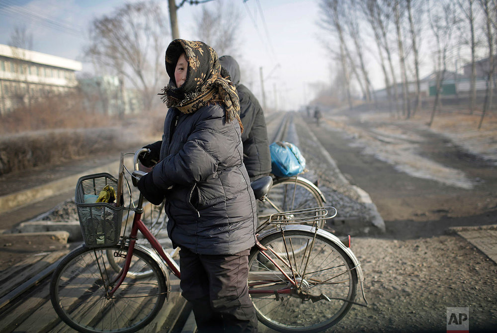 Women push their bicycles across a train track in the Chollima district of Nampo, a city and seaport located on the west coast of North Korea, on Jan. 7, 2017. (AP Photo/Wong Maye-E)
