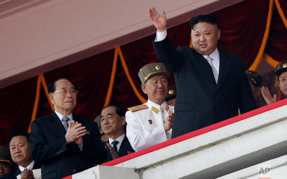 North Korean leader Kim Jong Un waves while officials, from left, Choe Ryong Hae, Kim Yong Nam, Pak Pong Ju, and Hwang Pyong So applaud during a military parade in Pyongyang on April 15, 2017. The parade was held to celebrate the 105th anniversary of the birth of Kim Il Sung, the country's late founder and grandfather of current ruler Kim Jong Un. (AP Photo/Wong Maye-E)