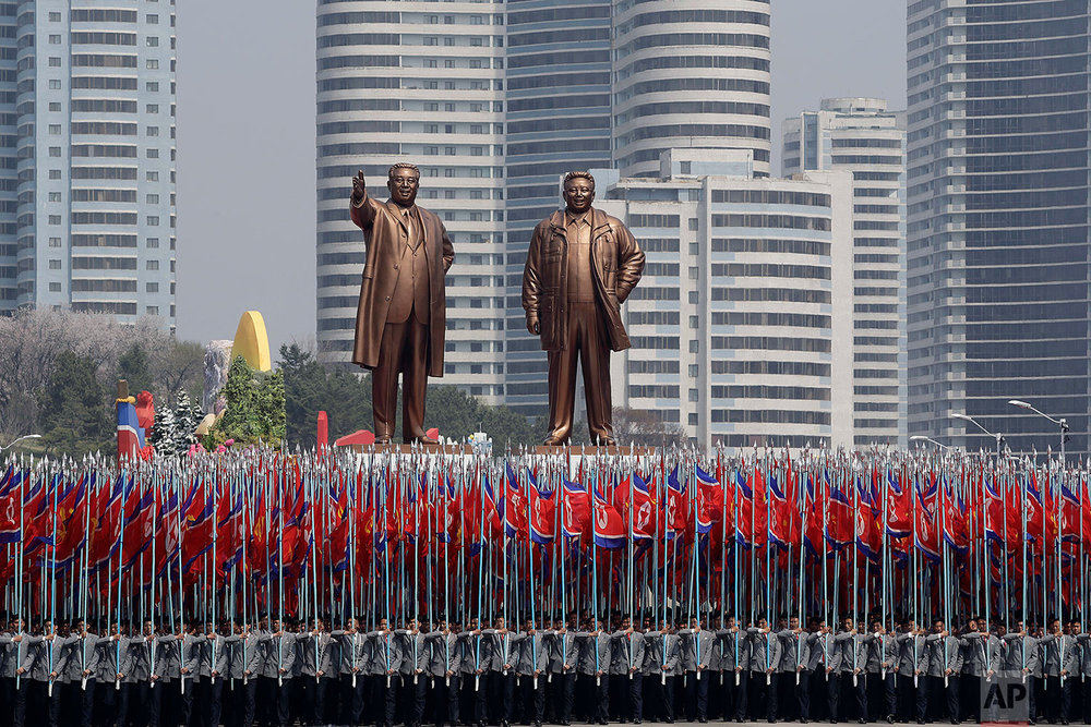 University students carry North Korean flags below bronze statues of the late leaders Kim Il Sung and Kim Jong Il on April 15, 2017, during a military parade in Pyongyang to celebrate the 105th anniversary of the birth of Kim Il Sung, the country's late founder and grandfather of current ruler Kim Jong Un. (AP Photo/Wong Maye-E)