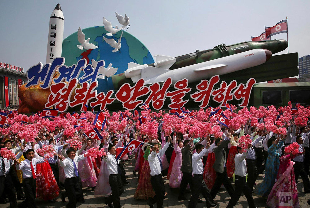 People wave flowers and flags as they march alongside a float displaying of models of various missiles along with doves on Kim Il Sung Square in Pyongyang, North Korea, during a military parade to celebrate the 105th anniversary of the birth of Kim Il Sung on April 15, 2017. (AP Photo/Wong Maye-E)