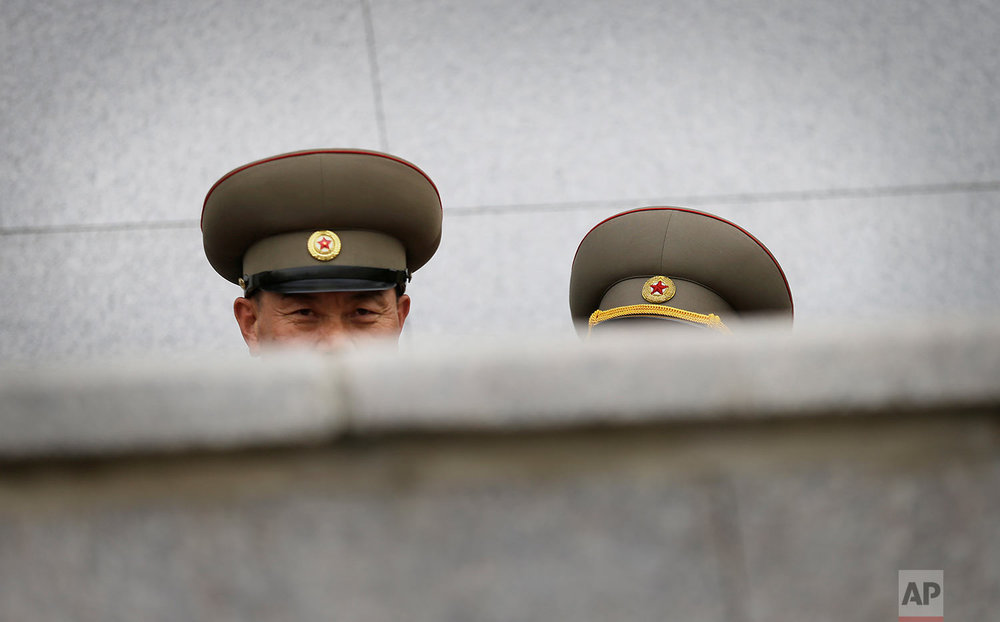 A military officer looks at foreign journalists from behind a balcony during a parade to celebrate North Korea's newly completed ruling-party congress at Kim Il Sung Square in Pyongyang on May 10, 2016. (AP Photo/Wong Maye-E)