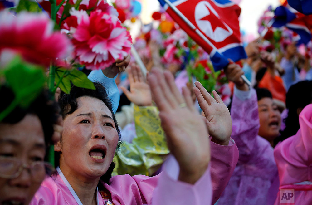 North Koreans wave decorative flowers as they walk past their leader, Kim Jong Un, during a parade in Pyongyang on Oct. 10, 2015. (AP Photo/Wong Maye-E)