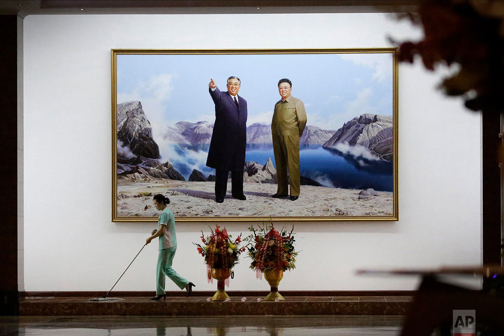 A staff member sweeps the floor in a hotel lobby in front of a picture featuring portraits of the late North Korean leaders Kim Il Sung, left, and Kim Jong Il on June 19, 2017, in Pyongyang, North Korea. (AP Photo/Wong Maye-E)