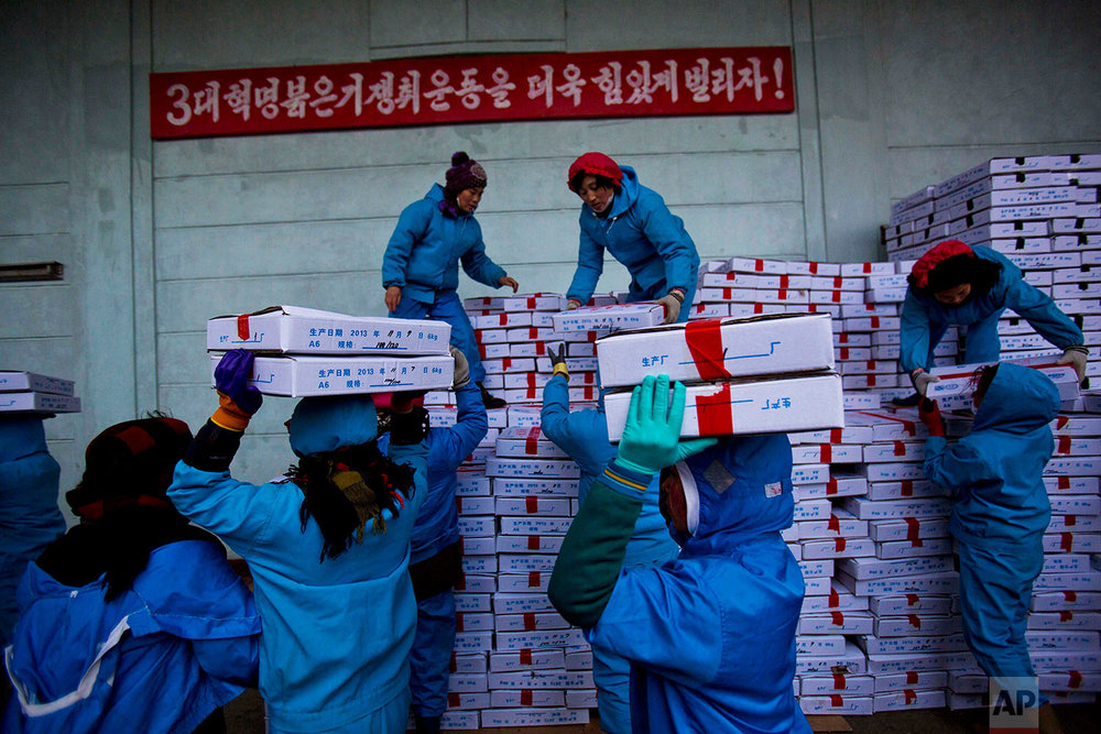 Workers carry boxes of seafood on Nov. 8, 2013, as they load a Chinese transport truck at the Suchae Bong Corp seafood factory in Rajin, North Korea, inside the Rason Special Economic Zone. (AP Photo/David Guttenfelder)
