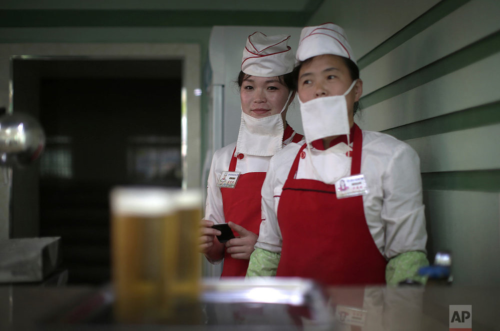 Beer servers Kim Yon Hui, left, and Yang Pok Yong wait to serve customers at the Taedonggang Beer shop in Pyongyang, North Korea, on May 7, 2016. (AP Photo/Wong Maye-E)
