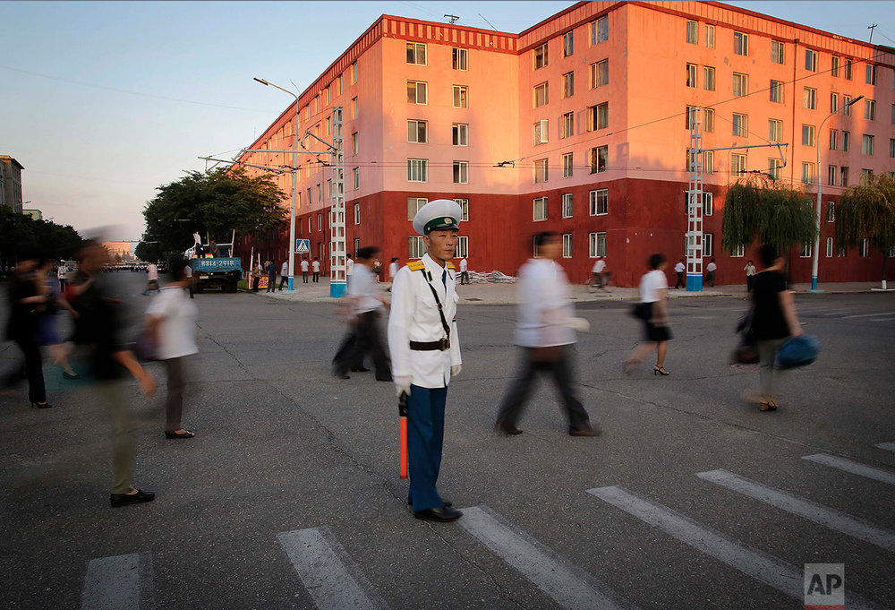 A traffic policeman directs pedestrians leaving an anti-U.S. rally that marked the 66th anniversary of the start of the Korean War at Kim Il Square in Pyongyang, North Korea, on June 25, 2016. (AP Photo/Wong Maye-E)